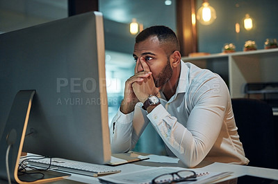 Buy stock photo Shot of a young businessman looking worried while working at his desk during late night at work