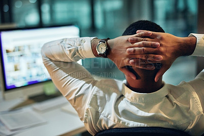 Buy stock photo Rearview shot of a young businessman taking a break at his desk during a late night in a modern office