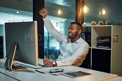 Buy stock photo Shot of a young businessman cheering while using a computer at his desk during a late night at work