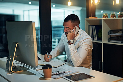 Buy stock photo Shot of a young businessman using a mobile phone and writing notes during a late night in a modern office