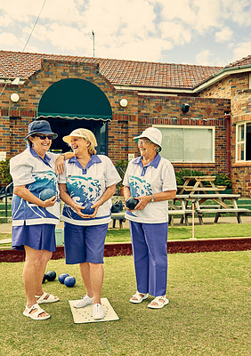 Buy stock photo Shot of a group of senior women playing a game of bowls together at a club