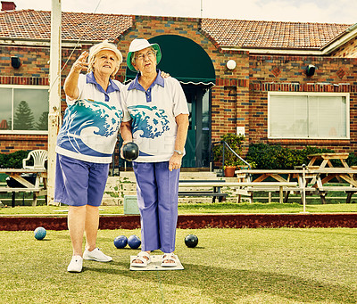 Buy stock photo Shot of two senior women playing a game of bowls together at a club