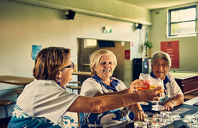 Buy stock photo Shot of three senior woman celebrating in the clubhouse with drinks after their game of bowls