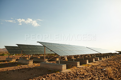 Buy stock photo Shot of a row of solar panels basking in the sun to generate electricity for the nearby holiday resort