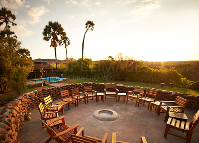 Buy stock photo High angle shot of a fire pit surrounded with chairs inside of a holiday resort during the late afternoon hours
