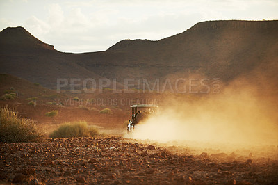Buy stock photo Rearview shot of a off road vehicle transporting guests through a holiday resort outside during the late afternoon hours