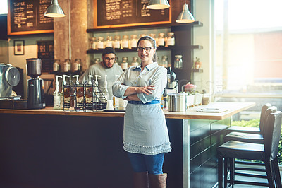 Buy stock photo Portrait of a young woman working in a cafe with her colleague in the background