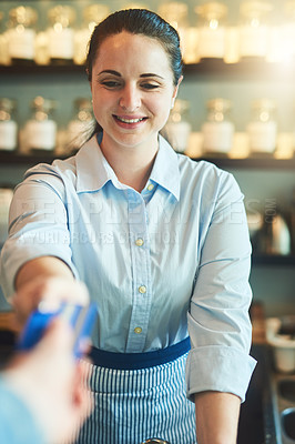 Buy stock photo Shot of a young woman receiving a credit card payment from a customer in a cafe