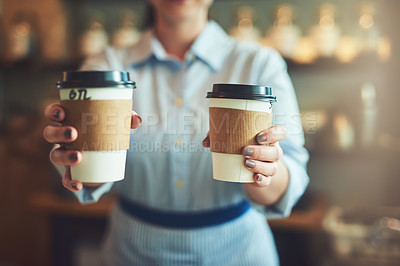 Buy stock photo Closeup shot of an unrecognizable barista holding cups of coffee in a cafe
