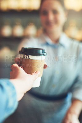 Buy stock photo Shot of a customer taking a cup of coffee from a barista in a cafe