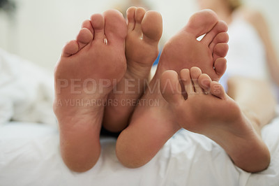 Buy stock photo Closeup shot of a couple's feet as they relax in bed at home