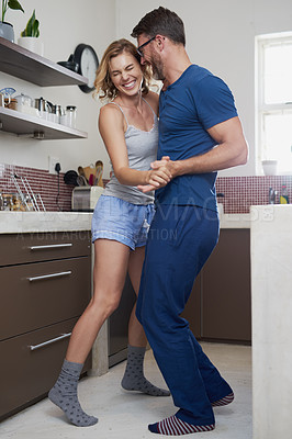 Buy stock photo Shot of a happy middle aged couple dancing in the kitchen at home