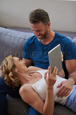 Buy stock photo Shot of a happy middle aged couple using a digital tablet together on the sofa at home