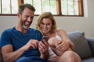 Buy stock photo Shot of a happy middle aged couple using a mobile phone together on the sofa at home