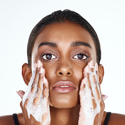 Buy stock photo Studio shot of a beautiful young woman washing her face against a light background