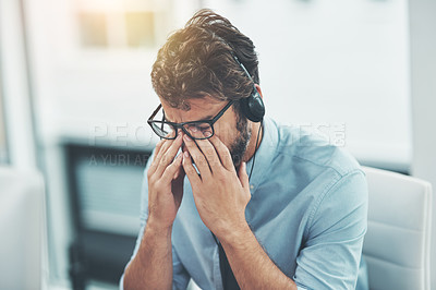 Buy stock photo Shot of a young man experiencing stress while working in a call center