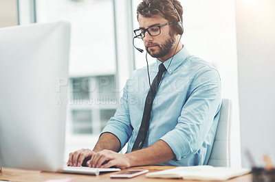 Buy stock photo Shot of a young man working in a call center