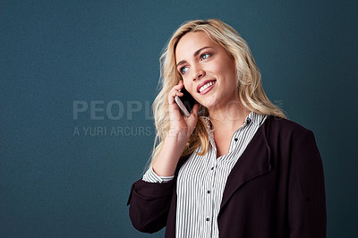 Buy stock photo Studio shot of a beautiful young businesswoman on a call against a blue background