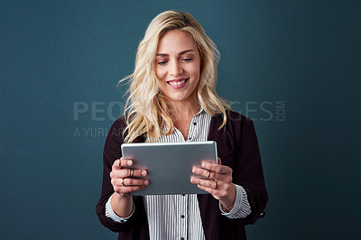 Buy stock photo Studio shot of a beautiful young businesswoman using a tablet against a blue background