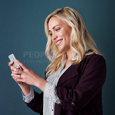 Buy stock photo Studio shot of a beautiful young businesswoman using a cellphone against a blue background