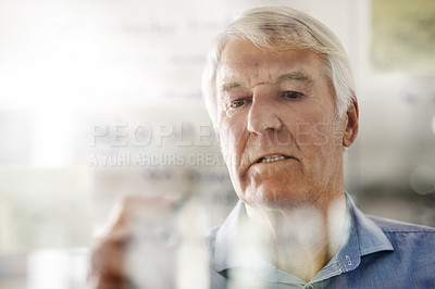 Buy stock photo Cropped shot of a senior businessman writing down ideas with a pen marker on a glass wall in the office
