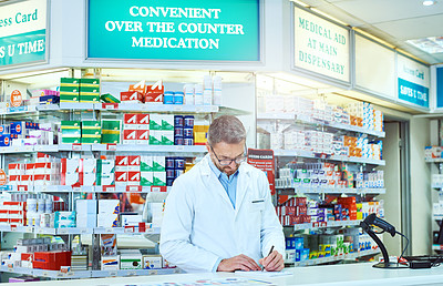 Buy stock photo Cropped shot of a handsome mature male pharmacist working in a pharmacy