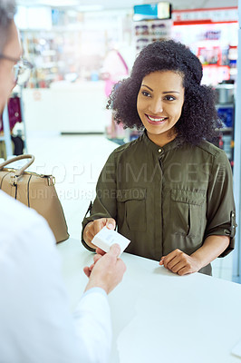 Buy stock photo Cropped shot of an attractive young female customer buying medication in a pharmacy