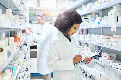 Buy stock photo Shot of a young woman doing inventory in a pharmacy with her colleague in the background