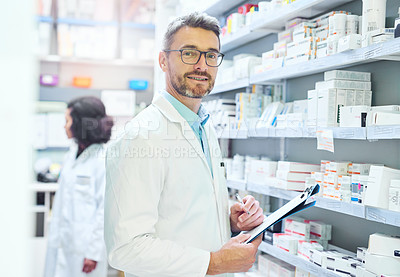 Buy stock photo Shot of a mature man doing inventory in a pharmacy with his colleague in the background