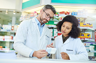 Buy stock photo Shot of a mature man and young woman discussing medication while working at a pharmacy