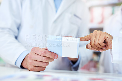 Buy stock photo Cropped shot of a man and woman discussing medication while working at a pharmacy