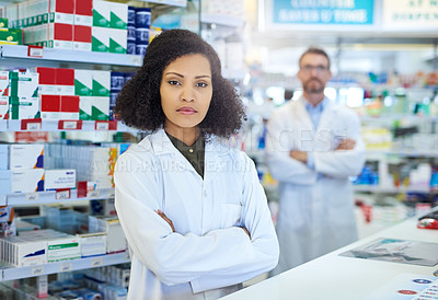 Buy stock photo Shot of a young woman working at the counter of a pharmacy with her colleague in the background