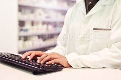 Buy stock photo Cropped shot of a pharmacist working on a computer in a pharmacy