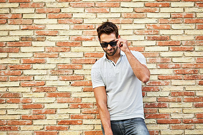 Buy stock photo Shot of a man talking on his cellphone while leaning against a brick wall