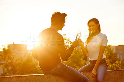 Buy stock photo Shot of a couple having champagne while on a rooftop date
