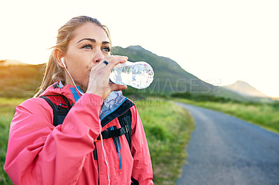 Buy stock photo Cropped shot of an attractive young female athlete drinking water while out for a morning run