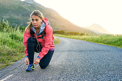 Buy stock photo Full length shot of an attractive young female athlete tying her laces before a morning run
