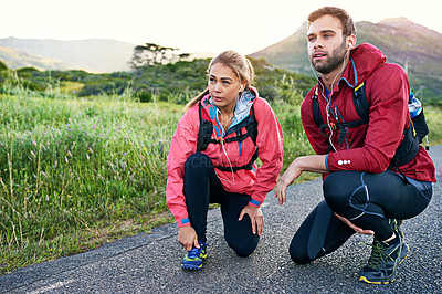 Buy stock photo Full length shot of a young couple tying their laces before a morning run