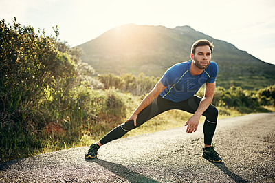 Buy stock photo Full length shot of a handsome young male athlete stretching before his run outdoors