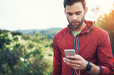 Buy stock photo Cropped shot of a handsome young male athlete checking his cellphone while out for a morning run
