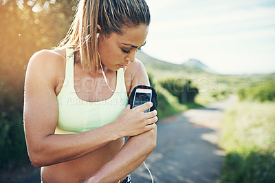 Buy stock photo Cropped shot of an attractive young female athlete preparing her playlist while out for a morning run