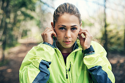 Buy stock photo Cropped portrait of an attractive young female athlete listening to music while out for a morning run