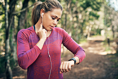 Buy stock photo Cropped shot of an attractive young female athlete tracking her pulse while out for a morning run