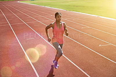 Buy stock photo Shot of a young athlete out running on the track