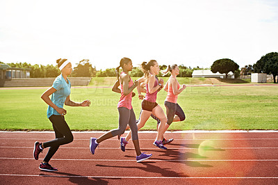 Buy stock photo Shot of a group of young athletes out running on the track