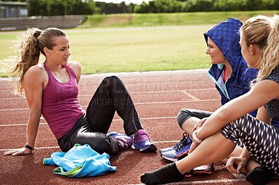 Buy stock photo Shot of a group of young athletes sitting out on the track after a run