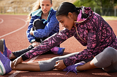 Buy stock photo Shot of young athletes out stretching on the track