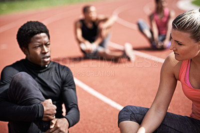 Buy stock photo Shot of young athletes sitting together on the track