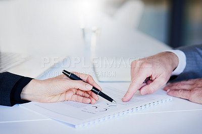 Buy stock photo Closeup shot of two unrecognizable businesspeople going through paperwork in an office