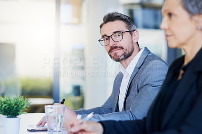 Buy stock photo Portrait of a mature businessman working alongside a colleague in an office